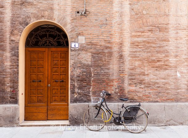 An old door and bicycle in Modena, Italy.